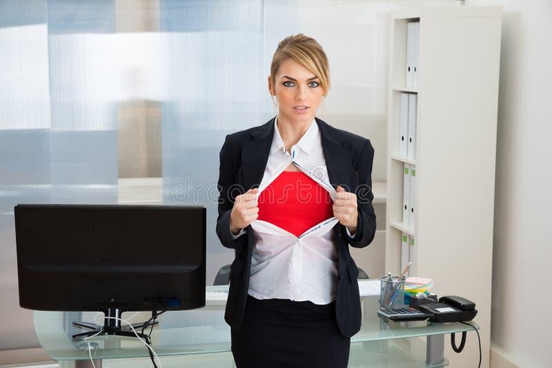 Bizneswoman pokazuje bohatera kostium obraz stock