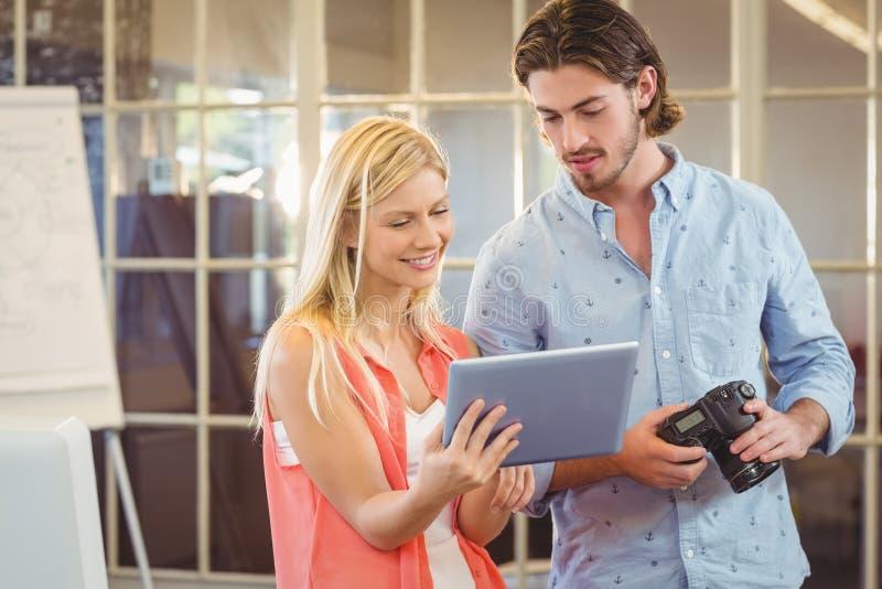 Bizneswoman pokazuje coś męski kolega na cyfrowej pastylce zdjęcia stock