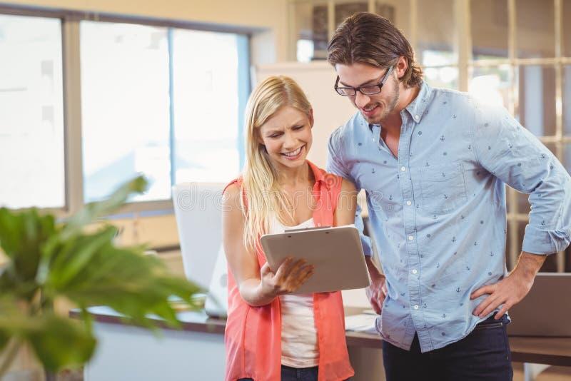 Bizneswoman pokazuje coś męski kolega na cyfrowej pastylce zdjęcie stock