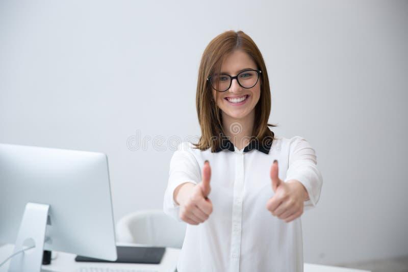 Bizneswoman pozycja z aprobatami w biurze obraz royalty free