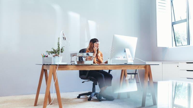 Bizneswoman pracuje na komputerowym obsiadaniu w biurze zdjęcia royalty free