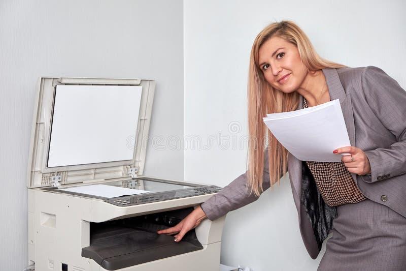 Bizneswoman pracuje na odbitkowej maszynie przy biurem zdjęcie stock