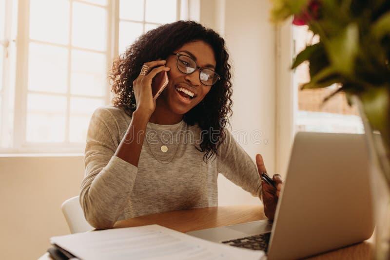 Bizneswoman pracuje od domu na laptopie i telefonie komórkowym zdjęcia stock