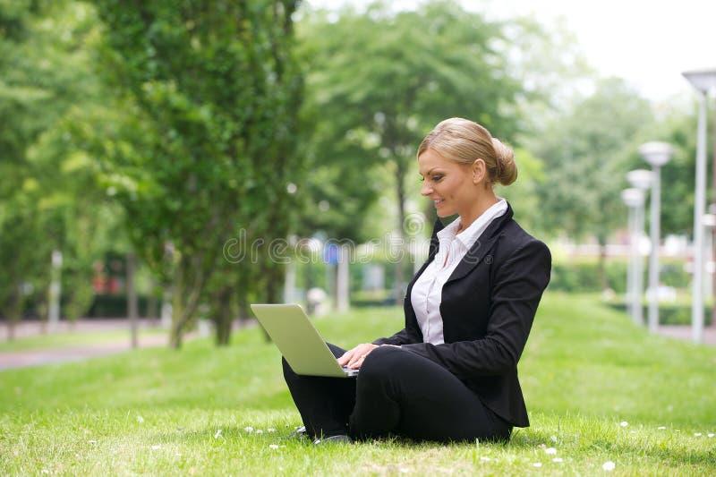 Bizneswoman pracuje outdoors na laptopie zdjęcie stock