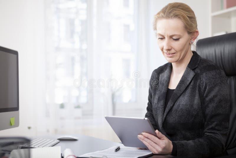 Bizneswoman przy jej Biurowym Używa pastylka komputerem zdjęcia royalty free