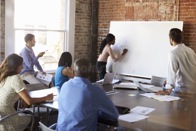 Bizneswoman Przy Whiteboard W Brainstorming spotkaniu zdjęcia stock