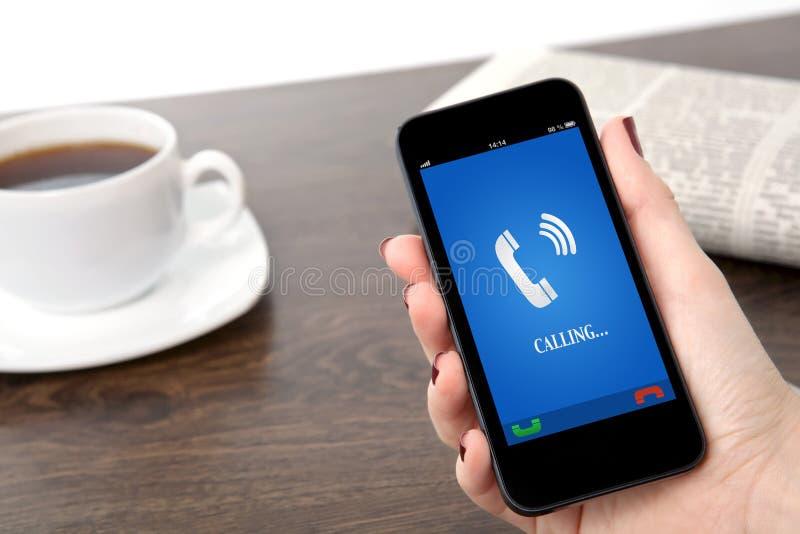 Bizneswoman ręka trzyma telefon z dzwonienie telefonu odbiorcą o obrazy royalty free