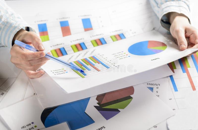 Bizneswoman ręki analizuje pieniężne statystyki fotografia stock