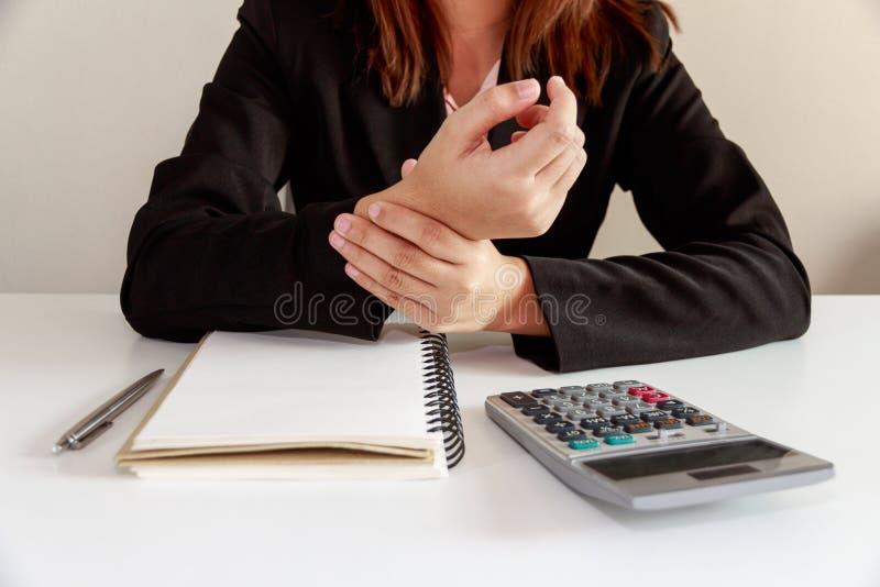 Bizneswoman ręki bolą na biurko biurowym syndromu z notatnikiem a zdjęcie royalty free