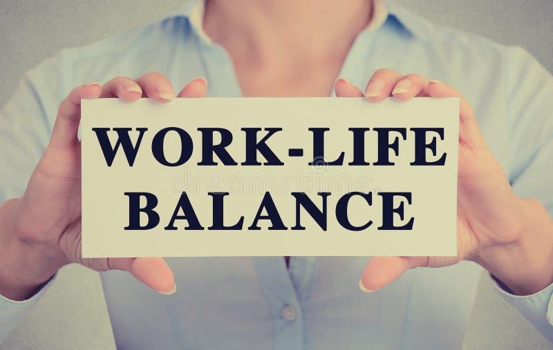 Bizneswoman ręki trzyma karta znaka z pracy życia równowagi wiadomością zdjęcie royalty free