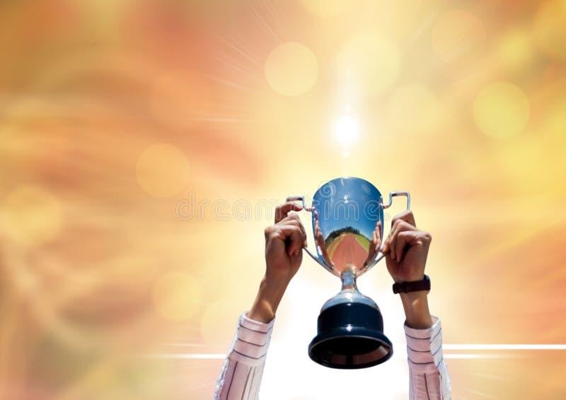bizneswoman ręki z trofeum Złocisty tło z racami fotografia stock