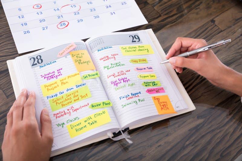 Bizneswoman Robi agendzie Na dzienniczku zdjęcie stock