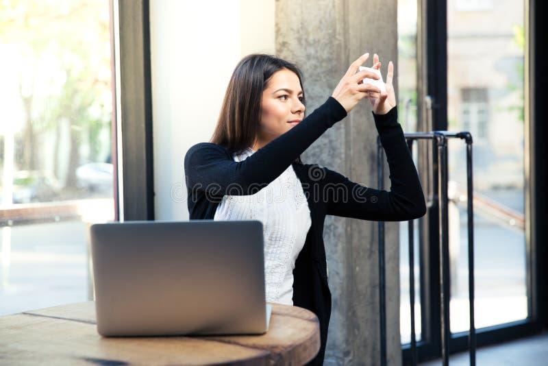 Bizneswoman robi fotografii na smartphone w kawiarni zdjęcie stock