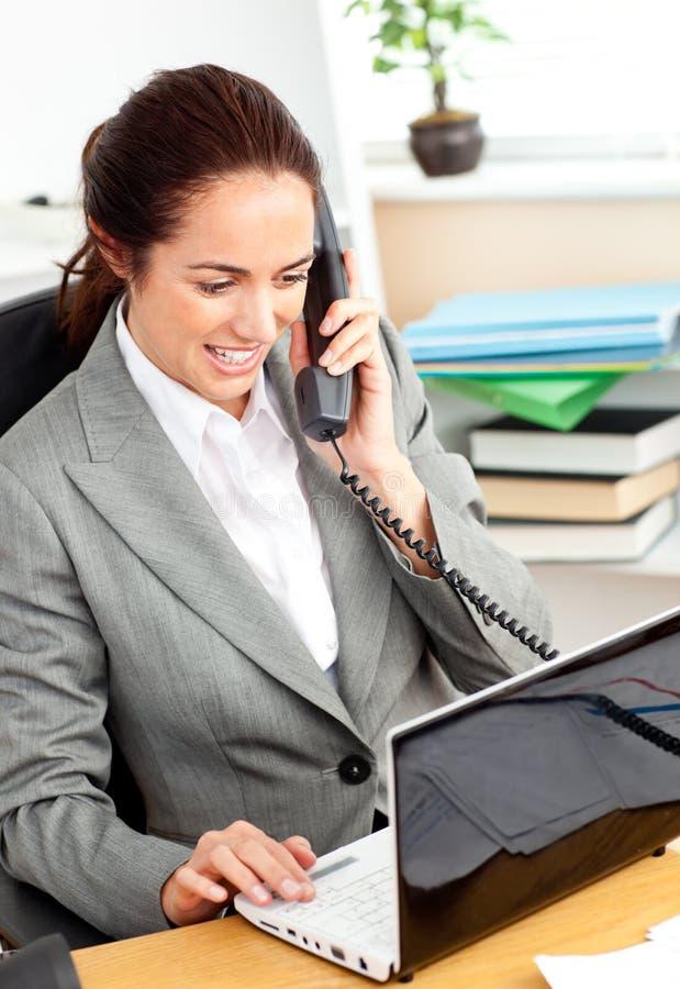 bizneswoman ruchliwie jej laptopu telefonowania używać zdjęcie stock