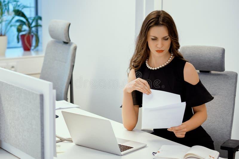 Bizneswoman siedzi przy biurkiem z komputerem i sprawdza dokumenty obraz stock