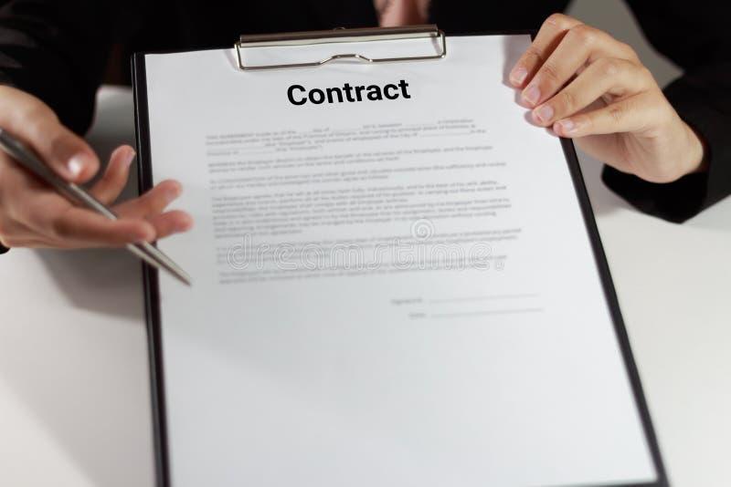Bizneswoman trzyma kontrakt i wskazuje przy jej d w kostiumu obrazy royalty free