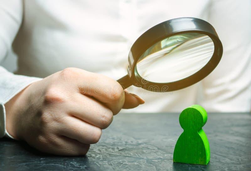 Bizneswoman trzyma powiększać - szkło nad zielonego mężczyzny postacią Rewizja dla utalentowanego pracownika Identyfikowań streng zdjęcie stock