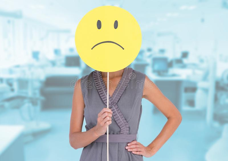 Bizneswoman trzyma smutną smiley twarz przed jej twarzą przeciw biuru w tle obrazy royalty free