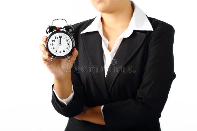 Bizneswoman trzyma zegaru alarm 12 am obrazy stock