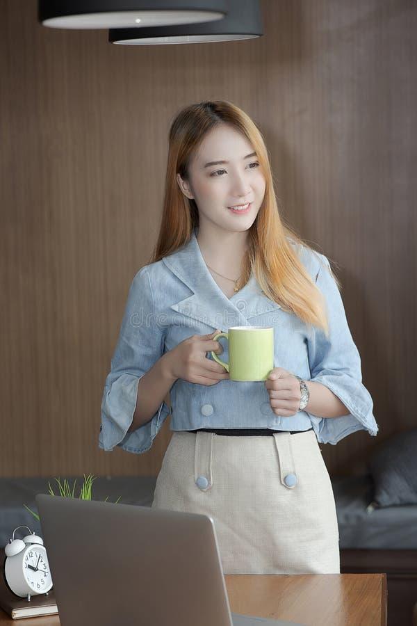Bizneswoman uśmiecha się zieloną filiżankę i trzyma w przypadkowej odzieży podczas gdy zdjęcia royalty free