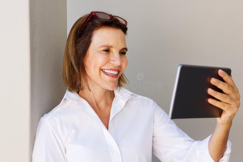 Bizneswoman uśmiechnięty i patrzeje cyfrową pastylkę obrazy royalty free