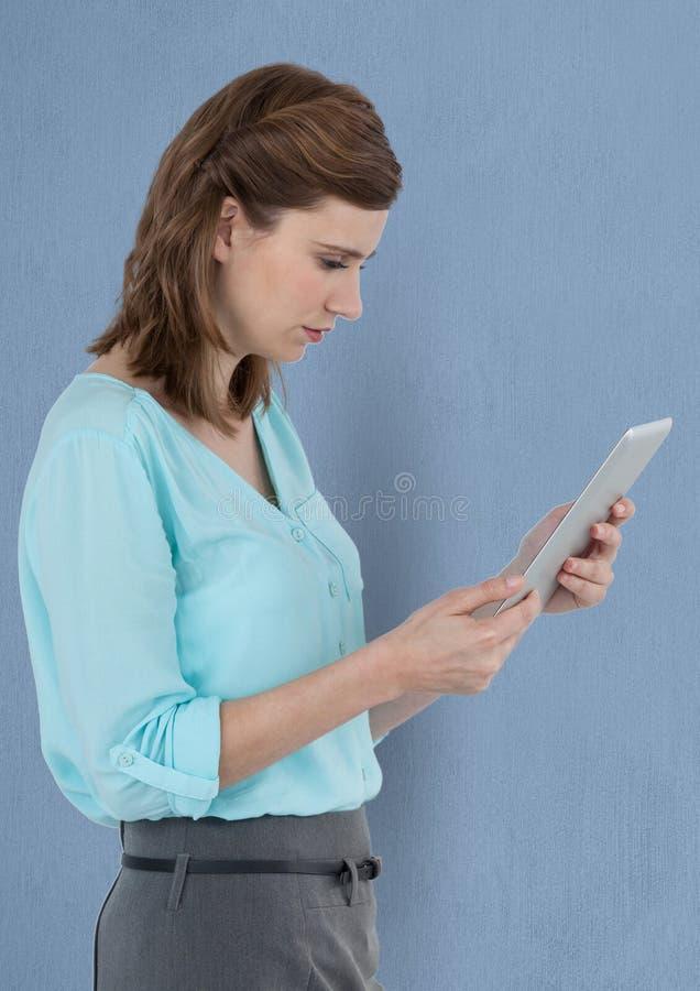 Bizneswoman używa cyfrową pastylkę nad błękitnym tłem fotografia stock