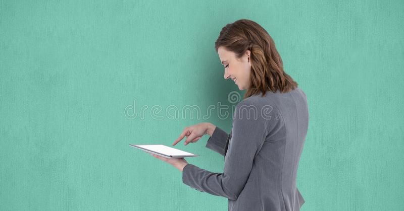 Bizneswoman używa cyfrową pastylkę przeciw zielonemu tłu obraz royalty free
