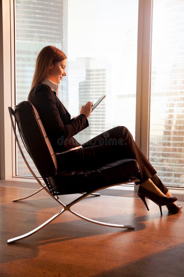 Bizneswoman używa cyfrową pastylkę w pokoju hotelowym obraz stock