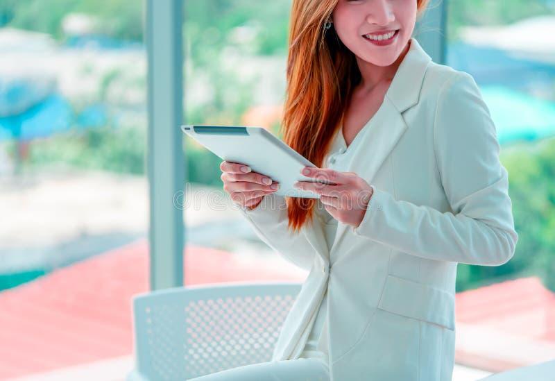 Bizneswoman używa cyfrową pastylki pozycję przed okno w miasto budynku zdjęcie royalty free
