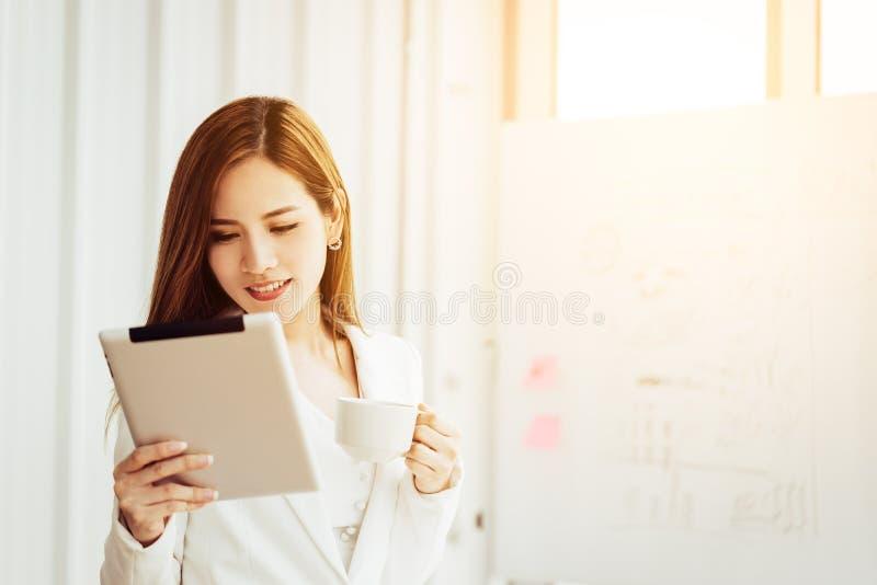 Bizneswoman używa cyfrową pastylki pozycję przed okno w miasto budynku zdjęcia royalty free