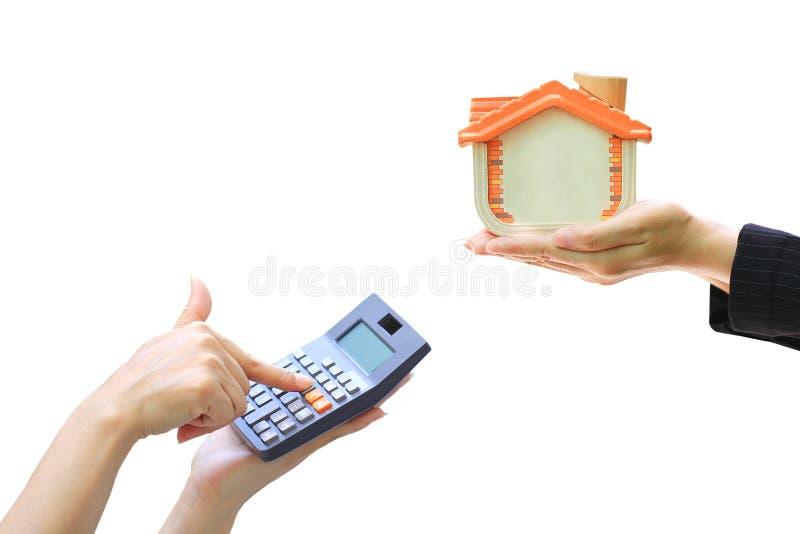 Bizneswoman używa drewnianego domu na białym tle i kalkulatora, księgowi kalkuluje zysk i stopy procentowej pojęcie zdjęcie stock