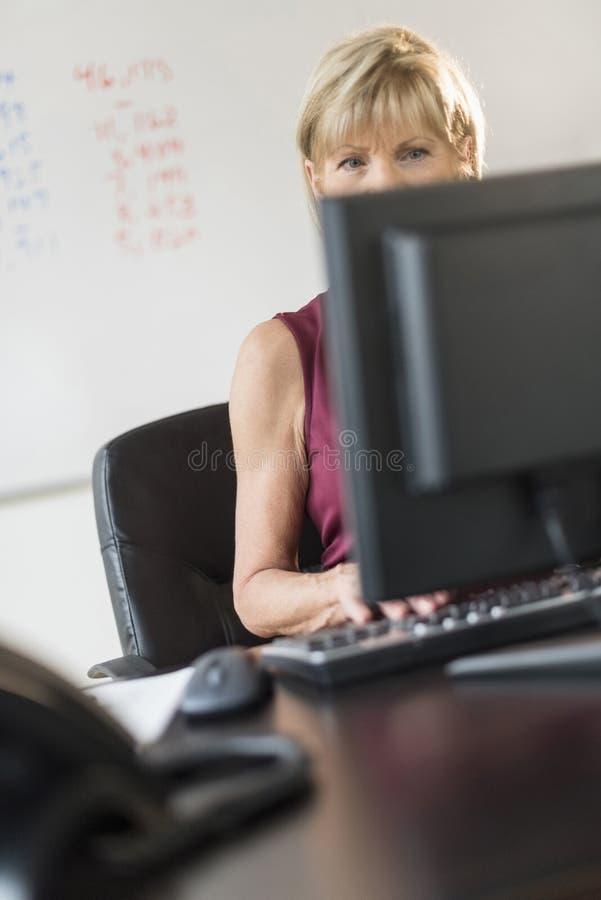 Bizneswoman Używa komputer stacjonarnego Przy biurkiem obrazy stock