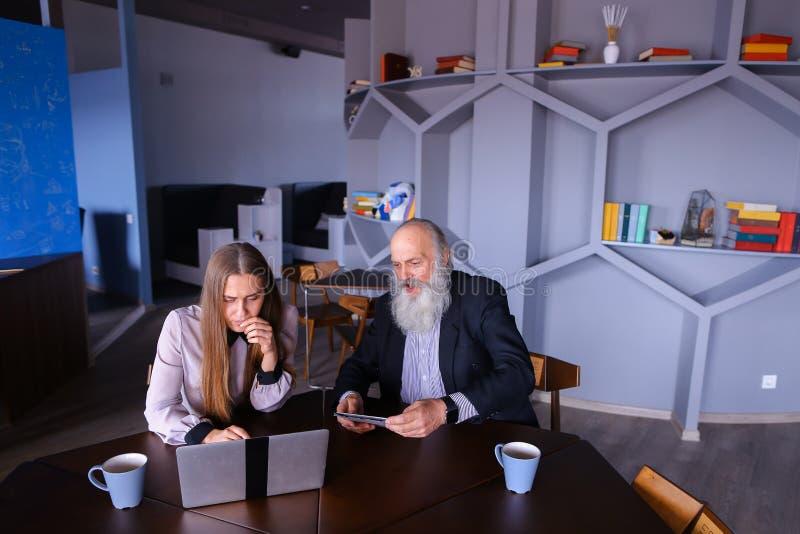 Bizneswoman używa laptop z starego człowieka kolegą w pomyślnym fotografia royalty free