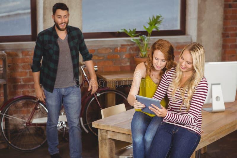 Bizneswoman używa pastylkę podczas gdy męski kolega patrzeje one fotografia royalty free