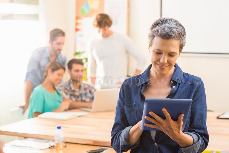Bizneswoman używa pastylkę z kolegami behind obraz stock