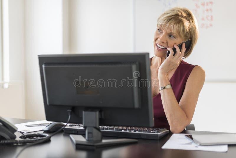Bizneswoman Używa telefon komórkowego Przy Komputerowym biurkiem obraz royalty free