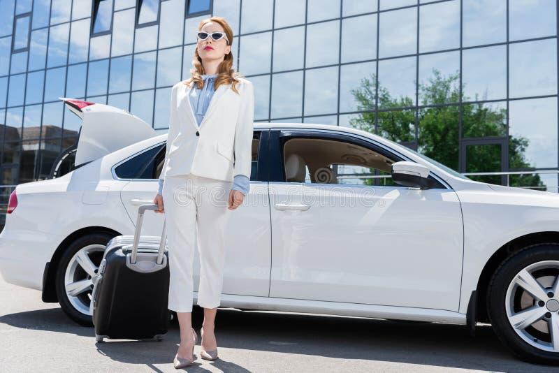 bizneswoman w białych okularach przeciwsłonecznych z walizki pozycją i kostiumu obrazy royalty free