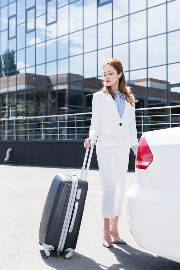bizneswoman w białym kostiumu z walizki pozycją zdjęcia royalty free