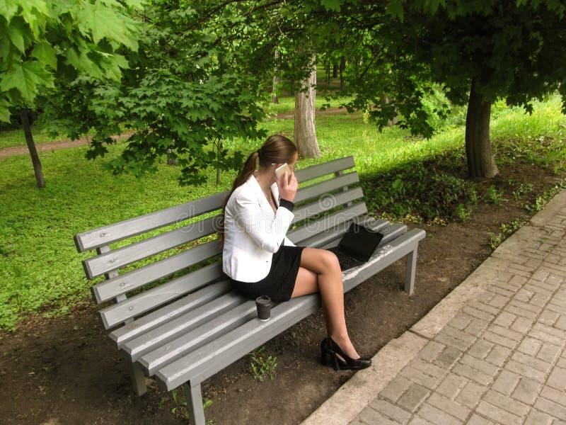 Bizneswoman w biurowym kostiumu opowiada na telefonie i spojrzenia przy laptopem ekranizują obsiadanie na ławce w parku, widok od obrazy royalty free
