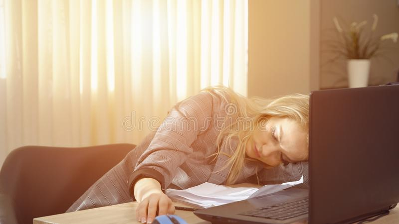 Bizneswoman w kostiumu ma drzemkę właśnie wyprostowywa na laptop klawiaturze po pracy zdjęcie stock