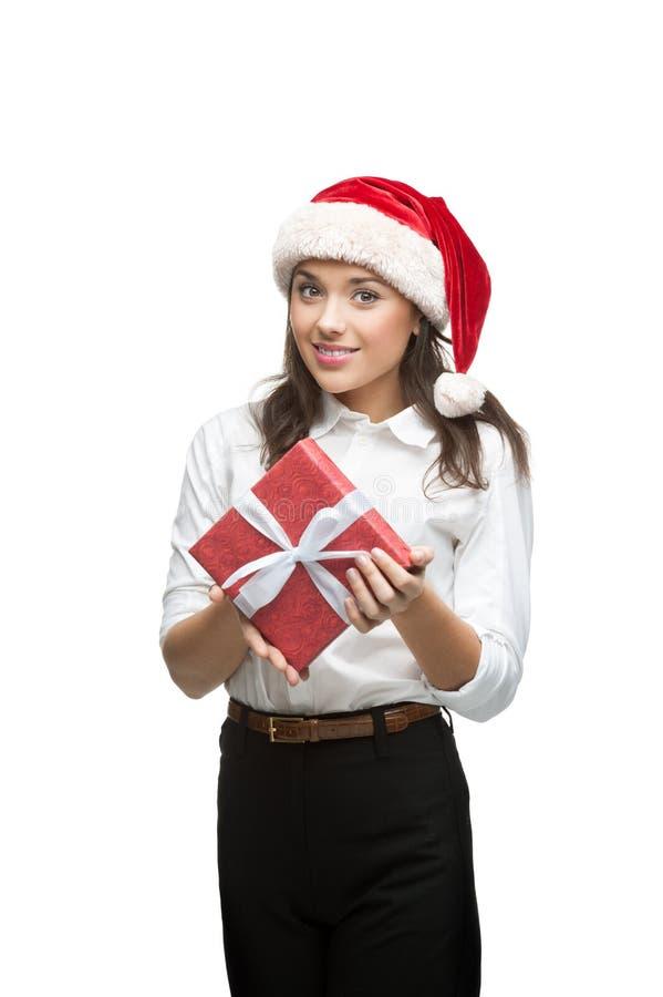Bizneswoman w Santa kapeluszowym mienia bożych narodzeń prezencie zdjęcia stock