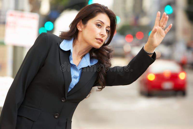 Bizneswoman Wita taxi W ruchliwej ulicie obraz royalty free