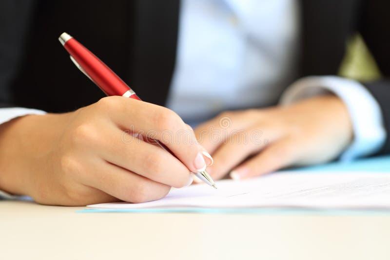 Bizneswoman wręcza writing w dokumencie fotografia royalty free