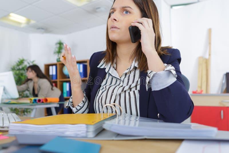 Bizneswoman wrzeszczy przy telefonem w biurze zdjęcia stock