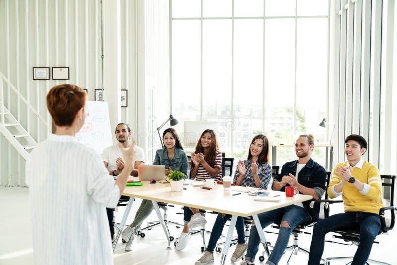 Bizneswoman wyjaśnia pomysły grupa kreatywnie różnorodna drużyna przy nowożytnym biurem Tylni widok gestykuluje ręki pozycję kier fotografia royalty free
