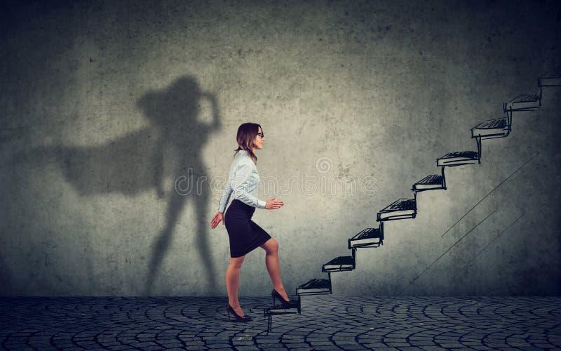 Bizneswoman wyobraża sobie być super bohaterem patrzeje aspirujący robić kariera planom zdjęcia stock