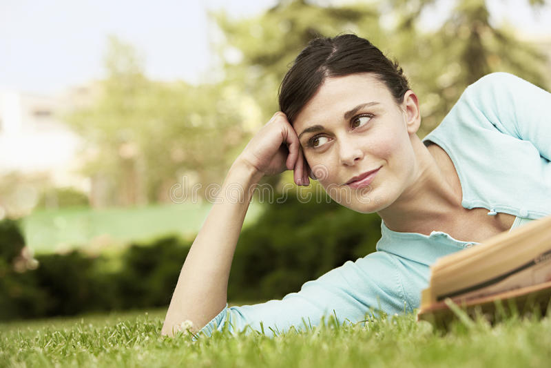Bizneswoman Z Gazetowym lying on the beach Na trawie obraz royalty free