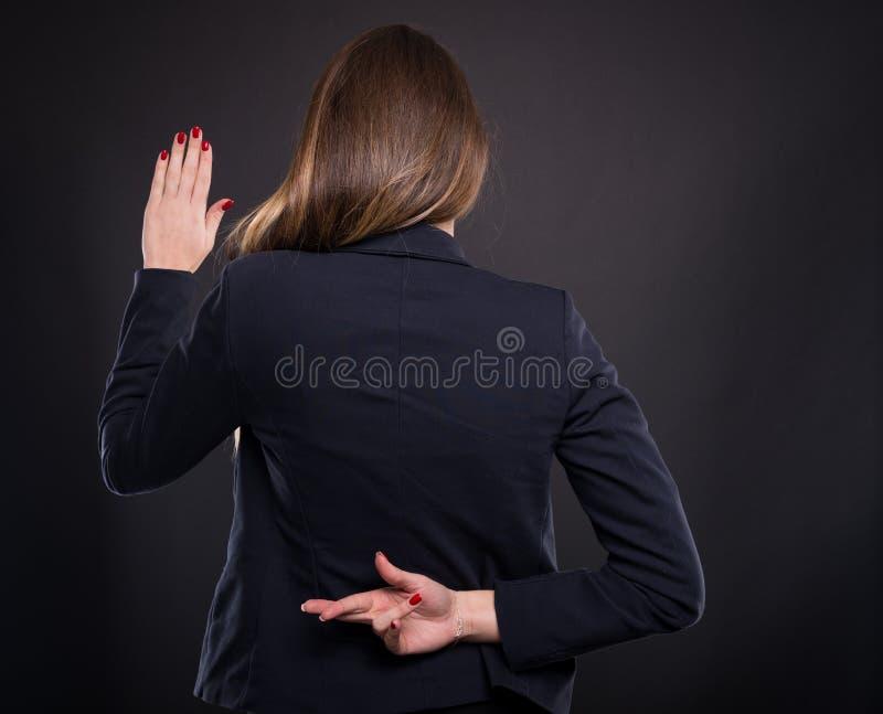 Bizneswoman z krzyżującymi palcami za ona z powrotem zdjęcia stock
