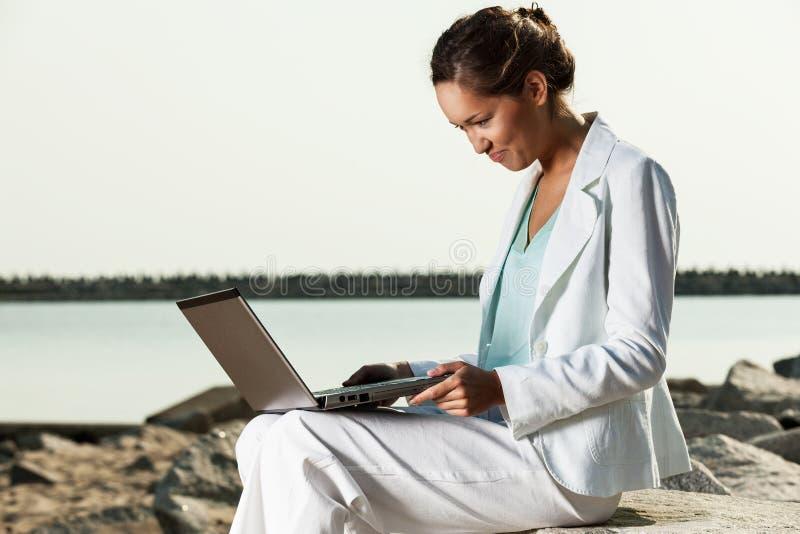 Bizneswoman z laptopu obsiadaniem na plaży zdjęcia royalty free
