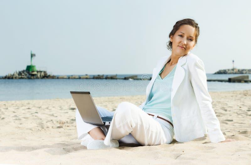 Bizneswoman z laptopu obsiadaniem na plaży obraz royalty free